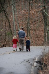 father and kids on walk down road through fall forest.