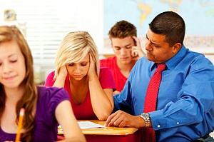 Teacher helps high school students at their desks.
