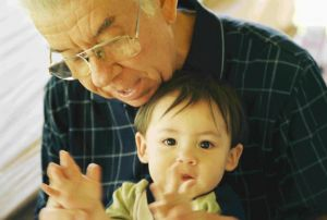 grandpa with young, dark-haired grandchild on lap